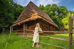 Junge Frau im ukrainischen nationalen Kostüm nahe altem Haus Stockbild