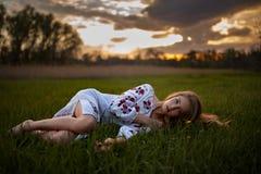 Junge Frau im ukrainischen Staatsangehörigen stickte Hemdlügen auf Gras in der Wiese bei Sonnenuntergang lizenzfreies stockbild