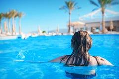 Junge Frau im Wasser in einem blauen Swimmingpool Stockfotografie