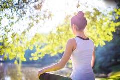 Junge Frau im weißen übenden Spitzenyoga in der schönen Natur Lizenzfreie Stockfotos