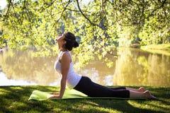 Junge Frau im weißen übenden Spitzenyoga in der schönen Natur Meditation am sonnigen Tag des Morgens Lizenzfreies Stockfoto