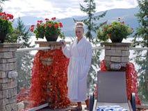 Junge Frau im weißen Bademantel, der durch Pool im Freien sich entspannt Lizenzfreie Stockfotografie