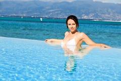 Junge Frau im weißen Bikini, der an den Feiertagen stillsteht stockfotos