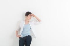 Junge Frau im weißen Hemd, das seine Hand über ihren Augen hält Geben Sie acht Schönes Mädchen auf einem weißen Hintergrund Raum  Stockfoto