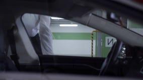 Junge Frau im weißen Hemd geht aus undeground Garage heraus und kommt in Auto stock video