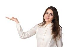 Junge Frau im weißen Hemd stellt sich mit einer Hand dar Lizenzfreie Stockbilder