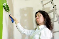 Junge Frau im wei?en Hemdumkippen mit einer gr?nen Farbe einer gemalten Wand stockbild