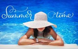 Junge Frau im weißen Hut, der in der Pool und Text Sommerzeit stillsteht Kalligraphiebeschriftungs-Handabgehobener betrag Lizenzfreie Stockbilder
