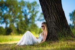 Junge Frau im weißen Kleid, das im Park sich entspannt Lizenzfreies Stockbild