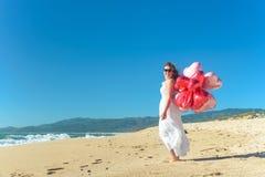 Junge Frau im weißen Kleid, das rote Ballone auf dem Strand hält Stockfotos