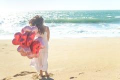 Junge Frau im weißen Kleid, das rote Ballone auf dem Strand hält Stockbild