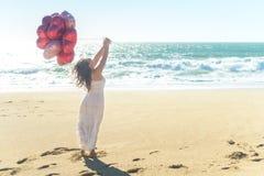 Junge Frau im weißen Kleid, das rote Ballone auf dem Strand hält Lizenzfreie Stockfotos