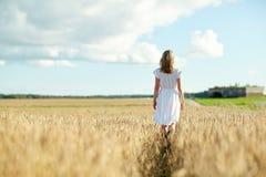 Junge Frau im weißen Kleid gehend entlang auf Feld stockfotografie