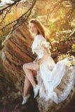 Junge Frau im weißen Kleid sitzt auf dem Stein unter den Niederlassungen lizenzfreies stockfoto