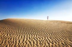 Junge Frau im weißen Kleid steht auf Düne in der Wüste am sonnigen heißen Tag Das Mädchen ist durstig Lizenzfreie Stockfotografie