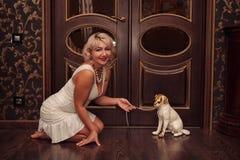 Junge Frau im weißen Kleid und in einem Hund Lizenzfreie Stockfotografie
