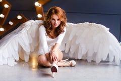 Junge Frau im weißen Bodysuit mit Engelsflügeln stockfotos