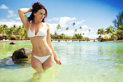 Junge Frau im weißen Bikini, der nahe bei Strand steht Lizenzfreie Stockfotos