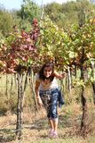 Junge Frau im Weinberg im Herbst in den italienischen Hügeln Stockfotos