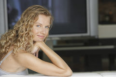 Junge Frau im Wohnzimmer mit Fernsehen im Hintergrund Stockfotos
