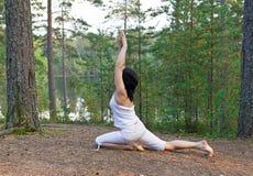 Junge Frau im Yoga eine mit Beinen versehene Königtaubenhaltung im Wald Stockfoto