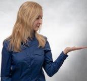Junge Frau im zufälligen blauen Hemd mit der offenen Hand, die zur Hand schaut lizenzfreies stockbild