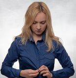 Junge Frau im zufälligen blauen Hemd oben ankleidend und unten schauend stockfotografie