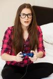 Junge Frau im zufälligen spielenden Videospiel Lizenzfreie Stockbilder