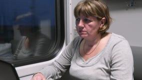 Junge Frau im Zug, die mit einem Laptop arbeitet stock footage