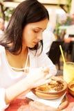 Junge Frau isst im Restaurant Stockbild