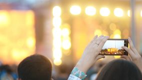 Junge Frau ist das Fotografieren des Musikkonzerts und draußen steht im Sommer stock video footage