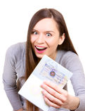 Junge Frau ist glücklich, ein Visum in ihrem Paß zu erhalten Stockfoto
