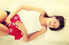 Junge Frau ist liegend zeigend und Magenschmerzen. Lizenzfreie Stockfotografie