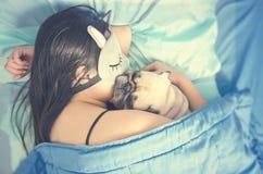 Junge Frau ist, schlafend liegend und mit nettem Pughundewelpen im Bett stockfoto