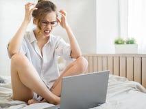 Junge Frau ist wegen etwas sehr verärgert, das sie auf ihrem Laptop sah Frustrierte Frau, die Laptop verwendet Lizenzfreies Stockbild