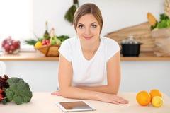 Junge Frau ist zum Kochen in einer Küche bereit Hausfrau, die am Tisch sitzt und die Kamera betrachtet Lizenzfreie Stockfotografie