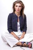 Junge Frau kleidete in der weißen Kleidung und im Matrosen an, die im Studio auf einem weißen Hintergrund aufwirft Lizenzfreie Stockbilder
