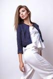 Junge Frau kleidete in der weißen Kleidung und im Matrosen an, die im Studio auf einem weißen Hintergrund aufwirft Lizenzfreie Stockfotos