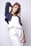 Junge Frau kleidete in der weißen Kleidung und im Matrosen an, die im Studio auf einem weißen Hintergrund aufwirft Stockfotografie