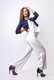 Junge Frau kleidete in der weißen Kleidung und im Matrosen an, die im Studio auf einem weißen Hintergrund aufwirft Stockfoto