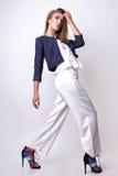 Junge Frau kleidete in der weißen Kleidung und im Matrosen an, die im Studio auf einem weißen Hintergrund aufwirft Lizenzfreie Stockfotografie