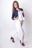 Junge Frau kleidete in der weißen Kleidung und im Matrosen an, die im Studio auf einem weißen Hintergrund aufwirft Stockbild