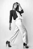 Junge Frau kleidete in der weißen Kleidung und im Matrosen an, die im Studio auf einem weißen Hintergrund aufwirft Schwarzweiss-F Stockfotos