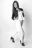 Junge Frau kleidete in der weißen Kleidung und im Matrosen an, die im Studio auf einem weißen Hintergrund aufwirft Schwarzweiss-F Stockfotografie
