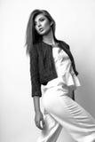 Junge Frau kleidete in der weißen Kleidung und im Matrosen an, die im Studio auf einem weißen Hintergrund aufwirft Schwarzweiss-F Lizenzfreie Stockbilder