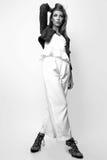 Junge Frau kleidete in der weißen Kleidung und im Matrosen an, die im Studio auf einem weißen Hintergrund aufwirft Schwarzweiss-F Lizenzfreie Stockfotos