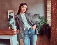 Junge Frau kleidete in einer grauen eleganten Jacke an, die Schale Mitnehmerkaffee beim Lehnen auf einer Tabelle in einem Raum mi stockbild