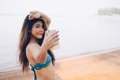 Junge Frau kleidete in Mode Badeanzug unter Verwendung des Handynehmens lizenzfreie stockbilder