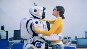 Junge Frau kommt zu einem menschlich ähnlichen Roboter, umarmen sie und sprechen stock footage