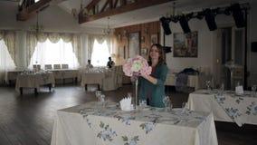 Junge Frau korrigiert eine Blumen-Anordnung auf dem Tisch, Blumen im hohen Glasvase, ein festlicher Tischschmuck und heiratet stock video